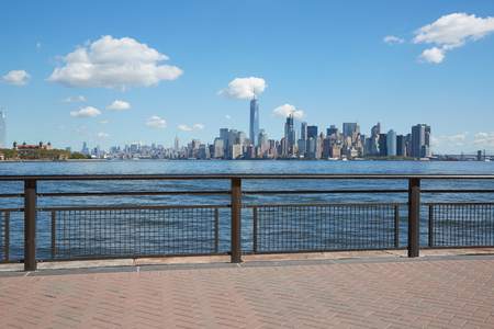 New York city skyline view from empty dock with railing in a sunny day