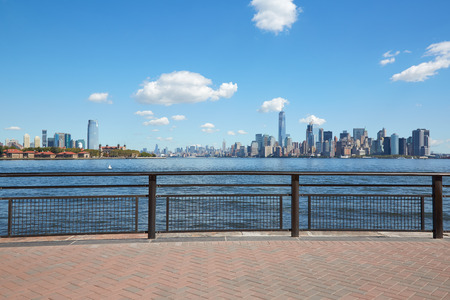 New York city skyline and Ellis Island view from empty dock terrace in a sunny day