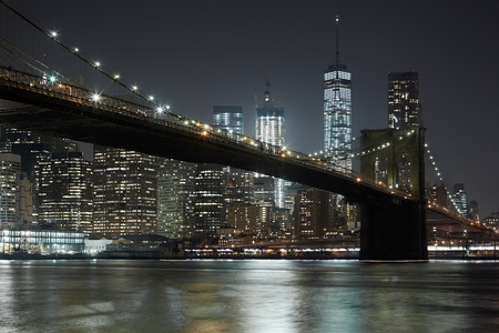 Brooklyn Bridge and New York city skyline illuminated at night Фото со стока - 73600583