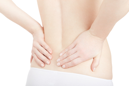 woman in pain: Young woman holds both hands on lower back, backache isolated on white, clipping path Stock Photo