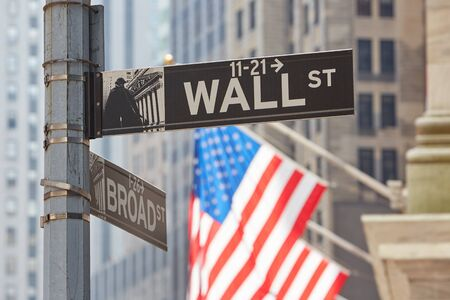 Wall Street sign near Stock Exchange with US flags, financial district in New York in a sunny day