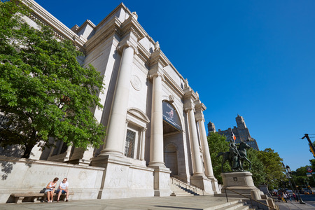 American Museum of Natural History building facade with people in a sunny day, clear blue sky on September 13, 2016 in New York. This is one of the largest museum of natural history of the world.
