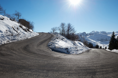winter road: Empty mountain road curve on Alps with snow on sides, blue sky in a sunny day