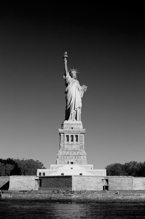 Statue of Liberty with pedestal and Liberty Island in a sunny day, New York in black and white