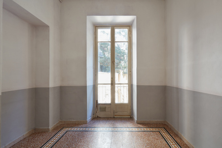 Empty room interior with old window and tiled floor in a sunny day