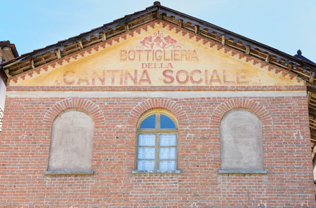 BAROLO, ITALY - AUGUST 6: Wine cellar and shop old sign painted on red bricks building facade on August 6, 2016 in Barolo, Italy. Editorial