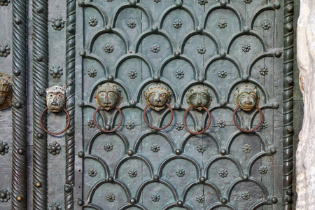 Venice, Saint Mark basilica portal with animal heads clappers texture background