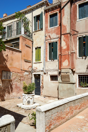 Venice court with ancient water well, buildings and houses facades in a sunny day in Italy Banco de Imagens