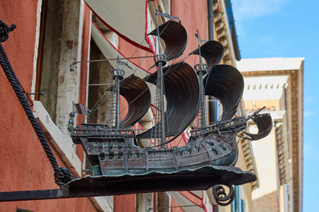 VENICE, ITALY - AUGUST 13, 2017: Sailing ship metal statue sign in a sunny summer day in Venice, Italy