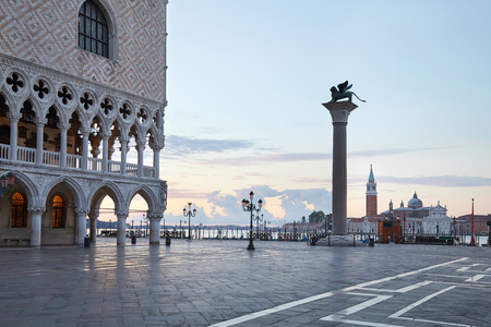 Saint Mark square in Venice with winged lion on column and pink sky in the early morning, Italy