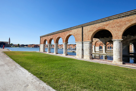 Venetian Arsenal with arcade, canal and green grass in a sunny day in Venice, Italy Фото со стока