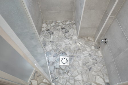 New shower with gray stones floor and tiled wall Stock Photo