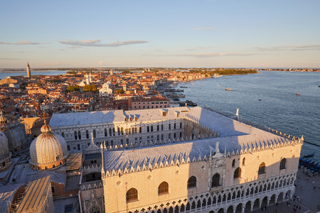 View of Venice from Saint Mark bell tower, castello district and lagoon at sunset in Italy