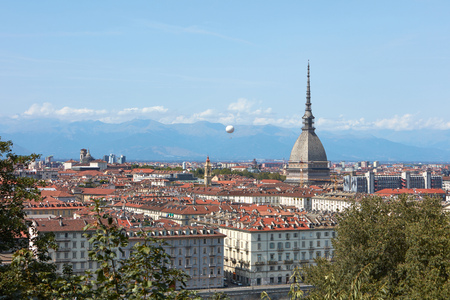 Turin rooftops view, Mole Antonelliana tower and hot air balloon in a sunny summer day in Italy