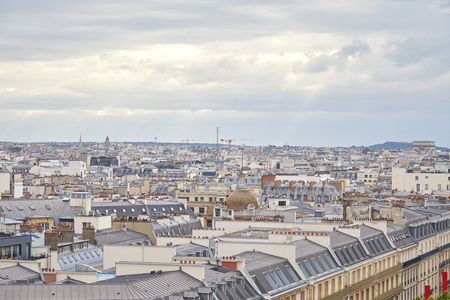 Paris rooftops view and city skyline in a cloudy day with sun beam in France Archivio Fotografico