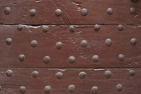 Old wooden brown door with nails texture background Imagens
