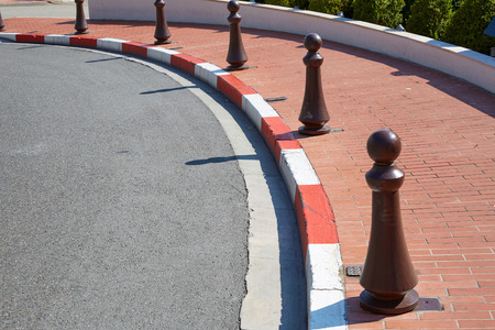 Monte Carlo street curve with formula one red and white signs detail in a sunny summer day in Monte Carlo, Monaco. Imagens