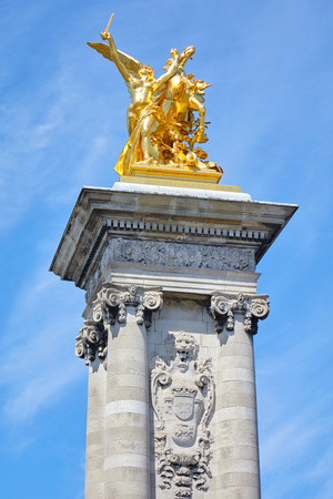 Alexandre III bridge golden statue with winged horse and column in a sunny summer day, blue sky in Paris, France.
