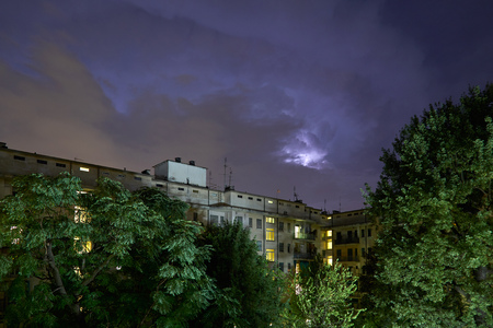 Buildings and green trees at night, illuminated sky during a lightning storm