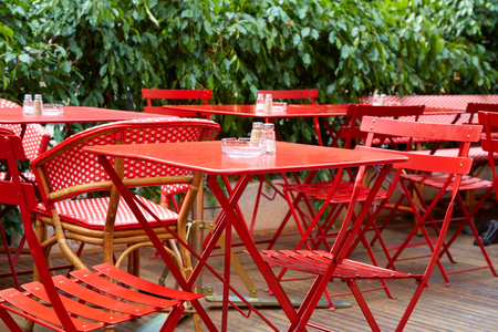 Outdoor restaurant red tables and chairs in summer