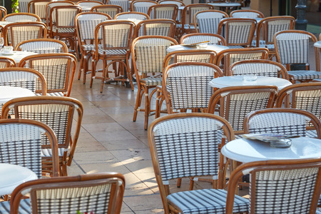 Outdoor cafe tables and chairs in a sunny summer day