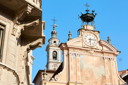 Saint Peter and Paul church clock and bell tower with automaton in a sunny summer day, blue sky in Mondovi, Italy.
