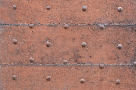 Old wooden, brown painted, door with nails texture background