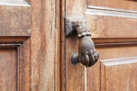 Old door knocker in shape of hand and wooden door background