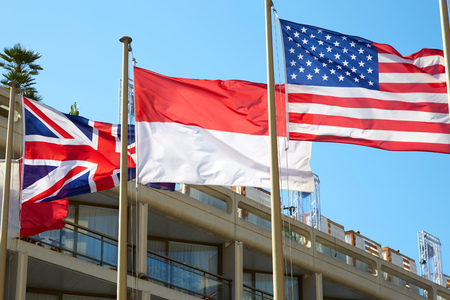Red and white Monaco flag with British and USA flag in a sunny summer day in Monta Carlo Imagens