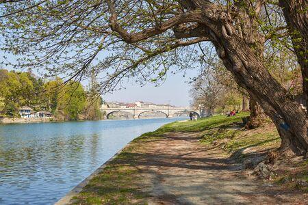 Po Flussuferweg mit Bäumen und Menschen an einem sonnigen Tag, blauer Himmel im Piemont, Turin, Italien