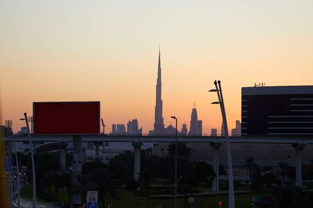 Dubai skyline with Burj Khalifa skyscraper at sunset, clear sky with flyover, billboards and street in United Arab Emirates