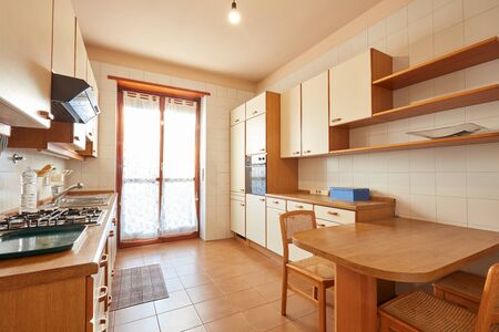 Kitchen interior with wooden table in a sunny day in normal apartment