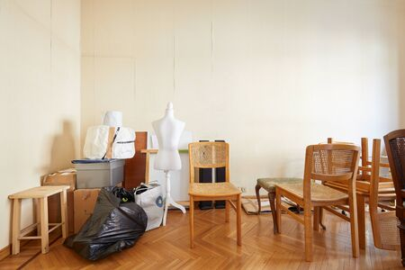 Room with chairs, boxes and a tailor dummy before moving house