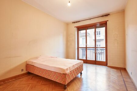 Bedroom with pink bed cover in old apartment interior