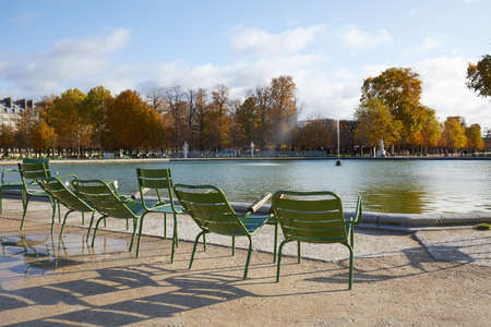 PARIS - NOVEMBER 7, 2019: Tuileries garden with green metal chairs and fountain in a sunny autumn day in Paris Editorial