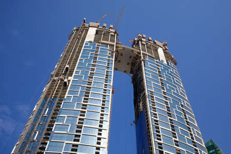 DUBAI, UNITED ARAB EMIRATES - NOVEMBER 23, 2019: Skyscrapers under construction with cranes, low angle view in a sunny day, clear blue sky in Dubai Sajtókép