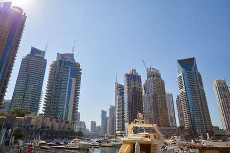 DUBAI, UNITED ARAB EMIRATES - NOVEMBER 23, 2019: Dubai Marina skyscrapers and harbor with boats in a sunny day, clear blue sky in Dubai