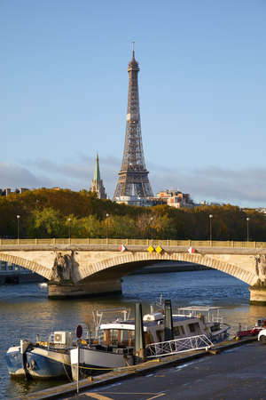 Eiffel tower, bridge and Seine river with boats in a sunny autumn day in Paris, France