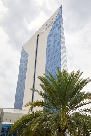 DUBAI, UNITED ARAB EMIRATES - NOVEMBER 21, 2019: Dubai Chamber of Commerce and Industry building and palm tree in a cloudy day Stock fotó