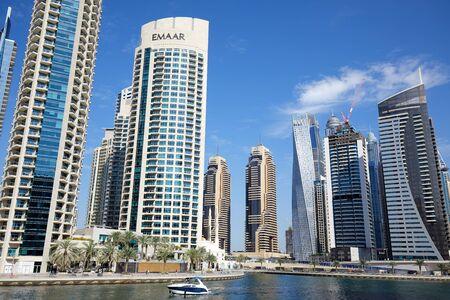 DUBAI, UNITED ARAB EMIRATES - NOVEMBER 23, 2019: Dubai Marina skyscrapers and canal with motorboat in a sunny day, clear blue sky in Dubai