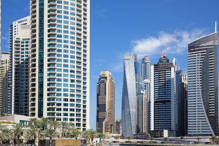DUBAI, UNITED ARAB EMIRATES - NOVEMBER 23, 2019: Dubai Marina skyscrapers and palm trees in a sunny day, blue sky in Dubai
