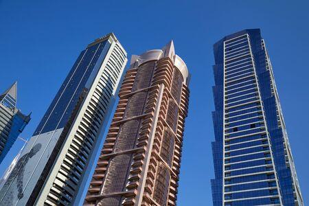 DUBAI, UNITED ARAB EMIRATES - NOVEMBER 23, 2019: Modern skyscrapers low angle view, clear blue sky in Dubai
