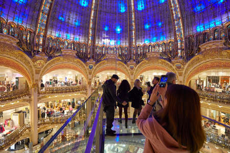 PARIS - NOVEMBER 6, 2019: Galeries Lafayette interior with Glasswalk installation with people and tourists in Paris Sajtókép