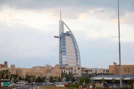 DUBAI, UNITED ARAB EMIRATES - NOVEMBER 21, 2019: Burj Al Arab luxury hotel with city view and cloudy sky in Dubai