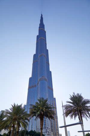 DUBAI, UNITED ARAB EMIRATES - NOVEMBER 22, 2019: Burj Khalifa skyscraper low angle view, clear blue sky with palm trees