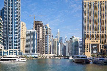 DUBAI, UNITED ARAB EMIRATES - NOVEMBER 23, 2019: Dubai Marina skyscrapers and canal with boats and yachts in a sunny day, clear blue sky in Dubai Sajtókép