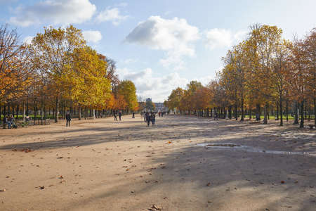 PARIS - NOVEMBER 7, 2019: Tuileries garden, walk with people in a sunny autumn day in Paris, wide angle view