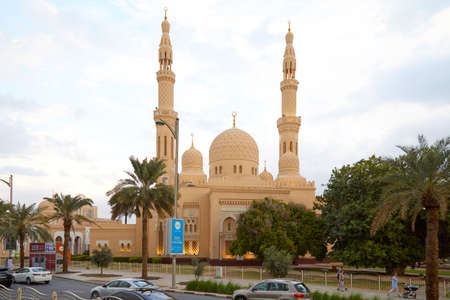 DUBAI, UNITED ARAB EMIRATES - NOVEMBER 21, 2019: Jumeirah mosque view with palm trees and people passing in the afternoon