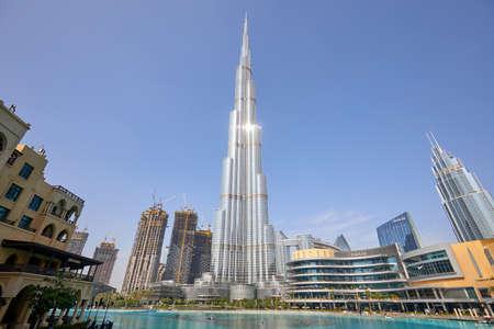 DUBAI, UNITED ARAB EMIRATES - NOVEMBER 19, 2019: Burj Khalifa skyscraper with sun reflection, Dubai Mall and artificial lake in a sunny day Sajtókép