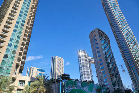 DUBAI, UNITED ARAB EMIRATES - NOVEMBER 23, 2019: Modern skyscrapers with palm trees in financial district, clear blue sky in Dubai